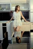 Εύθυμο χαμογελώντας νέο λευκό θηλυκό δερμάτων με τη μακροχρόνια τοποθέτηση τρίχας brunette στην κουζίνα στοκ φωτογραφία με δικαίωμα ελεύθερης χρήσης