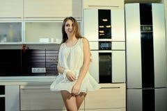 Εύθυμο χαμογελώντας νέο λευκό θηλυκό δερμάτων με τη μακροχρόνια τοποθέτηση τρίχας brunette στην κουζίνα στοκ φωτογραφίες