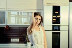 Εύθυμο χαμογελώντας νέο λευκό θηλυκό δερμάτων με τη μακροχρόνια τοποθέτηση τρίχας brunette στην κουζίνα στοκ φωτογραφία