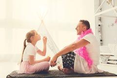 Εύθυμο χαριτωμένο κορίτσι που κάθεται απέναντι από τον πατέρα της στοκ φωτογραφία