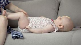 Εύθυμο χαριτωμένο κοριτσάκι που έχει τη διασκέδαση με τους γονείς στο σπίτι στις άνετες πάνες απόθεμα βίντεο