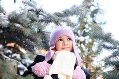 Εύθυμο όμορφο κορίτσι στο πορφυρό χειμερινό καπέλο Στοκ Φωτογραφία