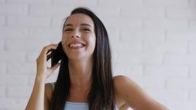 Εύθυμο brunette που μιλά στο τηλέφωνο απόθεμα βίντεο