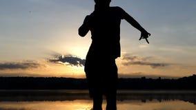 Εύθυμο disco χορών ατόμων σε μια τράπεζα λιμνών στο ηλιοβασίλεμα φιλμ μικρού μήκους