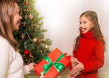Εύθυμο mom και το χαριτωμένο κορίτσι κορών της που ανταλλάσσουν τα δώρα Χριστούγεννα καλές διακ& στοκ φωτογραφίες