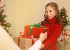 Εύθυμο mom και το χαριτωμένο κορίτσι κορών της που ανταλλάσσουν τα δώρα Χριστούγεννα καλές διακ& στοκ φωτογραφία με δικαίωμα ελεύθερης χρήσης