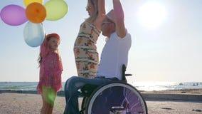 Εύθυμο mom, κόρη με τα μπαλόνια και μπαμπάς στο backlight, μικρό κορίτσι, μητέρα και με ειδικές ανάγκες πατέρας απόθεμα βίντεο