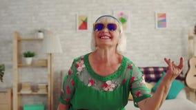 Εύθυμο rocker συνταξιούχων ηλικιωμένων γυναικών με την γκρίζα τρίχα στα γυαλιά που εξετάζουν το αργό MO καμερών απόθεμα βίντεο