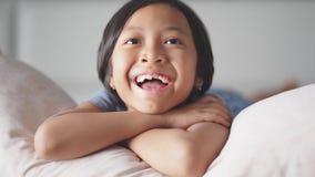 Εύθυμο toothless κορίτσι που προσέχει τη TV στην κρεβατοκάμαρα απόθεμα βίντεο