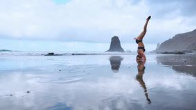 Εύκαμπτη γυναίκα γιόγκας που τεντώνει την μπροστινή κάμψη σχετικά με το μέτωπο στην παραλία θάλασσας ηλιοβασιλέματος γονάτων υπαί φιλμ μικρού μήκους