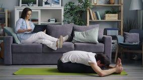 Εύκαμπτος νεαρός άνδρας που κάνει τη γιόγκα ενώ φίλη που χρησιμοποιεί τη συνεδρίαση lap-top στον καναπέ απόθεμα βίντεο