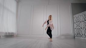 Εύκαμπτος ξανθός χορός άσκησης κοριτσιών εσωτερικός ενός στούντιο φιλμ μικρού μήκους