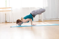 Εύκαμπτο κορίτσι που κάνει τις ισορροπώντας ασκήσεις μιγμάτων βραχιόνων, θέση λωτού peacock Στοκ Φωτογραφίες
