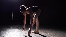 Εύκαμπτο νέο ballerina που στέκεται στα παπούτσια μπαλέτου pointe της στο επίκεντρο στο μαύρο υπόβαθρο στο στούντιο κίνηση αργή φιλμ μικρού μήκους