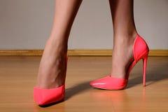 Εύμορφα πόδια γυναικών που φορούν στα μοντέρνα ρόδινα λουστραρισμένα με λάκκα υψηλά παπούτσια τακουνιών Στοκ Εικόνες