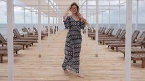 Εύμορφες γυναίκες που περπατούν χωρίς παπούτσια στην ξύλινη αποβάθρα στη θάλασσα, όμορφη γυναίκα που πηγαίνει ξυπόλυτη κατά μήκος φιλμ μικρού μήκους