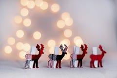 Ελάφια Χριστουγέννων σε μια σειρά σε ένα υπόβαθρο bokeh Στοκ εικόνα με δικαίωμα ελεύθερης χρήσης