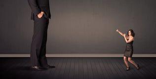Ελάχιστα bussineswoman μπροστά από μια γιγαντιαία κύρια έννοια ποδιών Στοκ εικόνες με δικαίωμα ελεύθερης χρήσης
