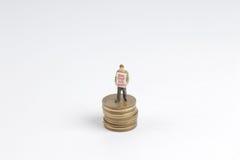 ελάχιστοι αριθμοί ανθρώπων που στέκονται στα νομίσματα Στοκ Εικόνα