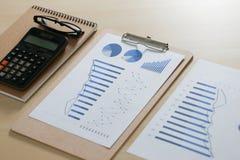 Ελέγχοντας την οικονομικές γραφική εργασία εκθέσεων και την επιχειρησιακή ομαδική εργασία επάνω Στοκ Εικόνα