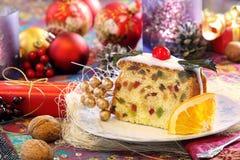 Ελαιόπρινος Χριστουγέννων fruitcake στο διακοσμημένο πίνακα Στοκ Φωτογραφία