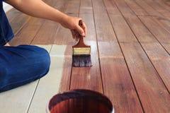 Ελαιόχρωμα ζωγραφικής χεριών στην ξύλινη χρήση πατωμάτων για το σπίτι που διακοσμείται, ho Στοκ Φωτογραφία