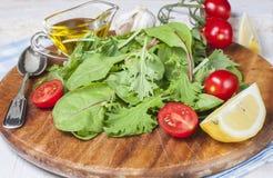 Ελαιόλαδο, φέτα λεμονιών και φρέσκες ντομάτες κερασιών ξύλινο boa Στοκ Εικόνες