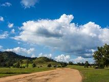 Εδαφολογικός δρόμος προς τον πράσινο λόφο, μπλε ουρανός Στοκ Εικόνα