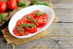 Ελαφριά σαλάτα ντοματών και arugula Εύγευστη και διαιτητική σαλάτα με τις ντομάτες, το arugula και τους σπόρους σουσαμιού σε ένα  Στοκ εικόνα με δικαίωμα ελεύθερης χρήσης