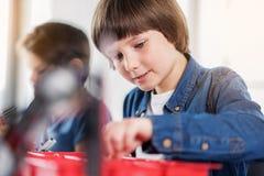 Ελαφριά χαμογελώντας αγόρι που εργάζεται στο ρομπότ Στοκ φωτογραφία με δικαίωμα ελεύθερης χρήσης