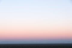 Ελαφρύς ουρανός βραδιού με τη ρόδινη μεταλαμπή και την ομίχλη Στοκ Εικόνες