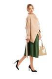 Ελαφρύ παλτό χρώματος, πράσινη φούστα και μαύρα παπούτσια με τα υψηλά τακούνια Στοκ Εικόνες