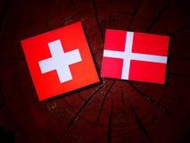 Ελβετική σημαία με τη δανική σημαία σε ένα κολόβωμα δέντρων που απομονώνεται στοκ φωτογραφία