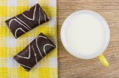 Ελβετικοί ρόλοι σοκολάτας στην πετσέτα και το φλυτζάνι του γάλακτος Στοκ Εικόνες