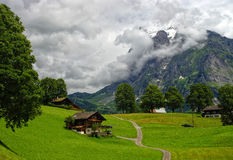 Ελβετικό τοπίο βουνών με το παραδοσιακό ξύλινο σαλέ σε Grindelwald Στοκ Φωτογραφία