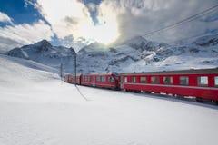 Ελβετικό τραίνο Bernina βουνών σαφές που διασχίζει μέσω του υψηλού MO Στοκ Εικόνες