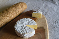 Ελβετικό Camembert τυρί και ένα τριγωνικό κομμάτι του τυριού σε έναν ξύλινο κατασκευασμένο πίνακα και ενός baguette σιταριού σε έ Στοκ Φωτογραφίες