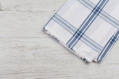 Ελεγμένη άσπρη μπλε πετσέτα κουζινών στο άσπρο αγροτικό ξύλινο υπόβαθρο Στοκ Φωτογραφία