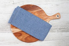 Ελεγμένη άσπρη μπλε πετσέτα κουζινών στο άσπρο αγροτικό ξύλινο υπόβαθρο Στοκ Φωτογραφίες