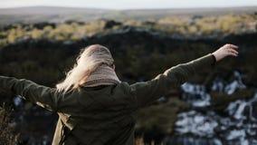 Ελευθερία: πίσω άποψη της νέας ευτυχούς γυναίκας που εξετάζει τον καταρράκτη Barnafoss στην Ισλανδία, την αύξηση του χεριού και τ απόθεμα βίντεο