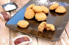 Ελεύθερα μπισκότα γλουτένης με την καρύδα και ημερομηνίες στο μαύρο πιάτο στο ξύλινο υπόβαθρο Στοκ Φωτογραφία