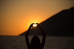 Ελεύθερη ευτυχής γυναίκα που απολαμβάνει το ηλιοβασίλεμα Αγκαλιάζοντας τη χρυσή πυράκτωση ηλιοφάνειας του ηλιοβασιλέματος, που απ Στοκ φωτογραφία με δικαίωμα ελεύθερης χρήσης