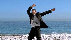 Ελεύθερος ευτυχής επιχειρηματίας που χορεύει στην παραλία απόθεμα βίντεο