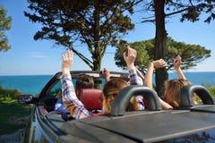 Ελεύθερος χρόνος, οδικό ταξίδι, ταξίδι και έννοια ανθρώπων - ευτυχείς φίλοι που οδηγούν στο αυτοκίνητο καμπριολέ κατά μήκος της ε Στοκ Φωτογραφίες