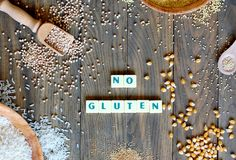 Ελεύθερο καλαμπόκι, ρύζι, φαγόπυρο, quinoa, κεχρί και αμάραντος δημητριακών γλουτένης με το κείμενο καμία γλουτένη στο γκρίζο ξύλ Στοκ Εικόνες