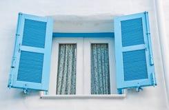 Ελληνικά παράθυρα ύφους με τα μπλε αναδρομικά ξύλινα παραθυρόφυλλα Στοκ Φωτογραφία