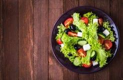 Ελληνικά σαλάτα & x28 μαρούλι, ντομάτες, τυρί φέτας, αγγούρια, μαύρο olives& x29  στη σκοτεινή ξύλινη τοπ άποψη υποβάθρου Στοκ Φωτογραφία