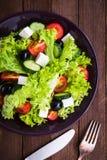 Ελληνικά σαλάτα & x28 μαρούλι, ντομάτες, τυρί φέτας, αγγούρια, μαύρο olives& x29  στη σκοτεινή ξύλινη τοπ άποψη υποβάθρου Στοκ φωτογραφίες με δικαίωμα ελεύθερης χρήσης