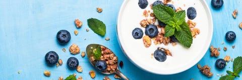 Ελληνικά granola και βακκίνια γιαουρτιού στον μπλε πίνακα Στοκ φωτογραφία με δικαίωμα ελεύθερης χρήσης