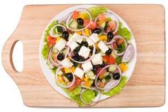 Ελληνική σαλάτα κατά μια άσπρη τοπ άποψη πιάτων Στοκ φωτογραφία με δικαίωμα ελεύθερης χρήσης